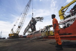 Workers unload the fuselage of AirAsia QZ8501, which crashed into the Java Sea on Dec. 28, from the ship Onyx Crest in Tanjung Priok port in Jakarta