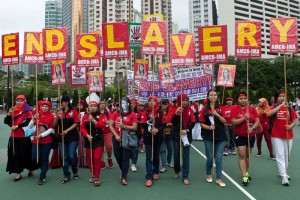 "Migrant workers from Indonesia carry placards which collectively read ""End Slavery"" during a Labour Day rally in Hong Kong on May 1, 2014. Over a thousand protesters gathered for the annual May Day rally in Hong Kong's landmark Victoria Park to walk towards the government headquarters waving colourful flags and placards, while singing a Chinese version of the famous ""Do you hear the people sing?"" from the musical Les Miserables, calling for better working conditions and better wages.  AFP PHOTO / ANTHONY WALLACEANTHONY WALLACE/AFP/Getty Images"