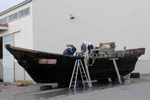 This picture taken on November 24, 2015 shows coast guard officials investigating a wooden boat at the Fukui port in Sakai city in Fukui prefecture, western Japan after the ship was found drifting off the coast of Fukui. Japan is investigating nearly a dozen suspicious boats recently found drifting off the country's coastline, some with decaying bodies aboard, officials said on November 27, as media speculated they came from North Korea. At least 11 cases involving wooden boats -- some badly damaged -- with 20 bodies on board have been reported during October and November.   AFP PHOTO / JIJI PRESS    JAPAN OUT / AFP / JIJI PRESS / JIJI PRESS        (Photo credit should read JIJI PRESS/AFP/Getty Images)